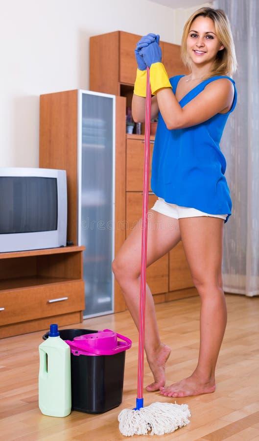 Νοικοκυρά που χαμογελά και που κάνει το πάτωμα που καθαρίζει στο εσωτερικό στοκ εικόνες με δικαίωμα ελεύθερης χρήσης
