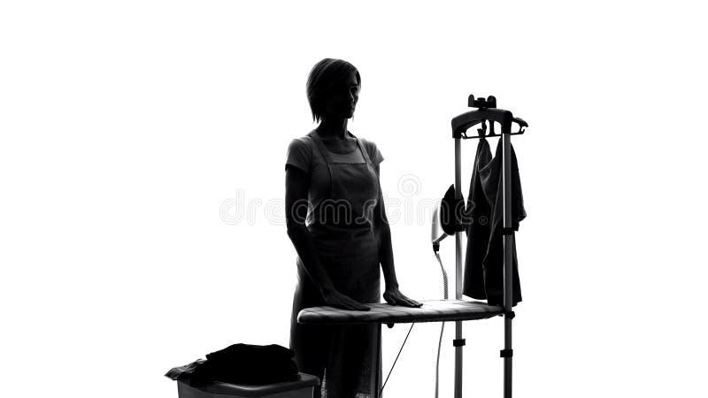 Νοικοκυρά στην ποδιά που στέκεται κοντά στο σιδέρωμα του πίνακα, υπηρεσία πλυντηρίων, βοήθεια οικιακών στοκ φωτογραφία