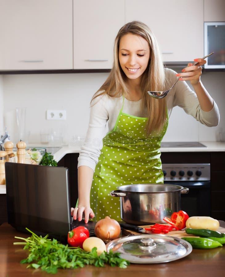 Νοικοκυρά στο μαγείρεμα arpon με το lap-top στοκ εικόνα με δικαίωμα ελεύθερης χρήσης