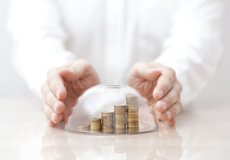 Νομίσματα αύξησης που προστατεύονται κάτω από έναν θόλο και τα χέρια γυαλιού στοκ φωτογραφία
