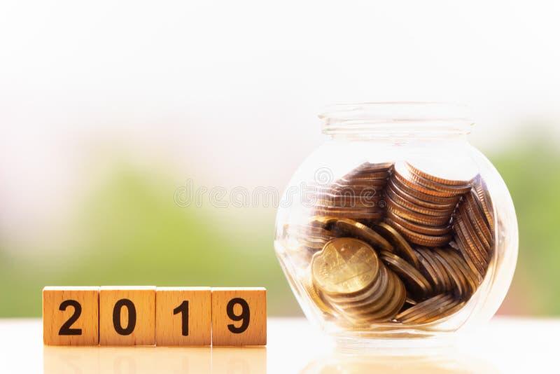 Νομίσματα και ξύλινη λέξη 2019 φραγμών στο υπόβαθρο φύσης αποταμίευση χρημάτων στοκ εικόνες