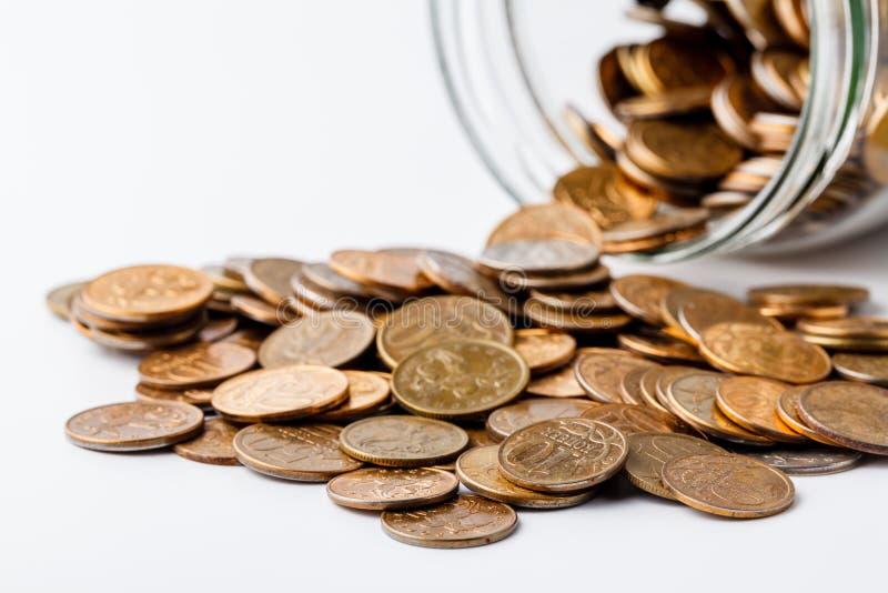 Νομίσματα που τοποθετούνται στο βάζο γυαλιού και νομίσματα που διασκορπίζονται γύρω από το βάζο γυαλιού στοκ φωτογραφία με δικαίωμα ελεύθερης χρήσης