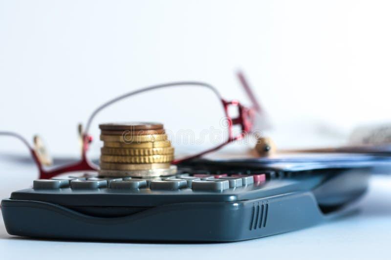 Νομίσματα στον υπολογιστή, eyeglass, μολύβι στοκ φωτογραφία με δικαίωμα ελεύθερης χρήσης