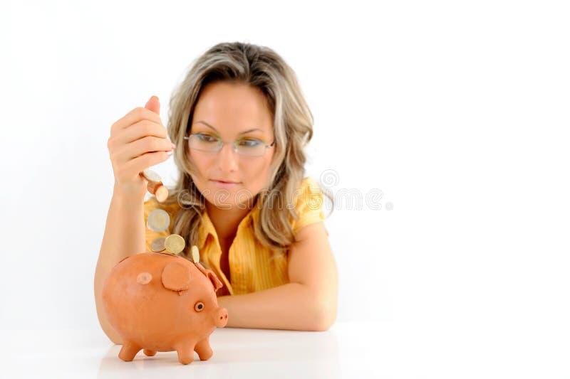 νομίσματα τραπεζών που ρίχνουν το κορίτσι πέρα από piggy στοκ εικόνα