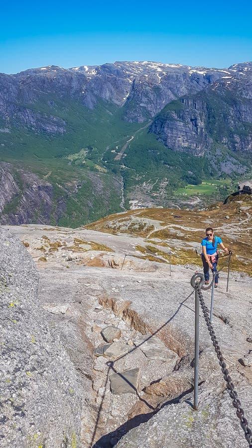 Νορβηγία - ένα κορίτσι που αναρριχείται επάνω σε έναν απότομο βράχο στοκ εικόνα
