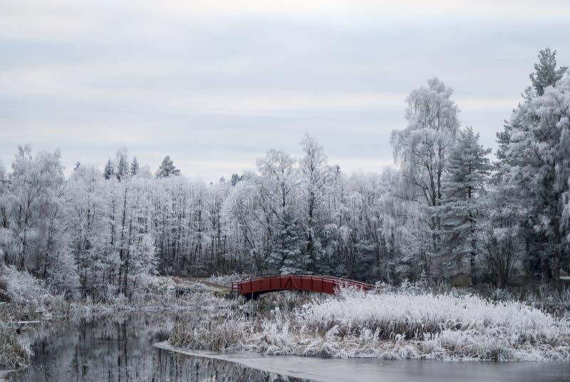 Νορβηγία το χειμώνα, το νορβηγικό τοπίο, τον ήρεμο ποταμό και την κόκκινη γέφυρα στοκ εικόνες με δικαίωμα ελεύθερης χρήσης