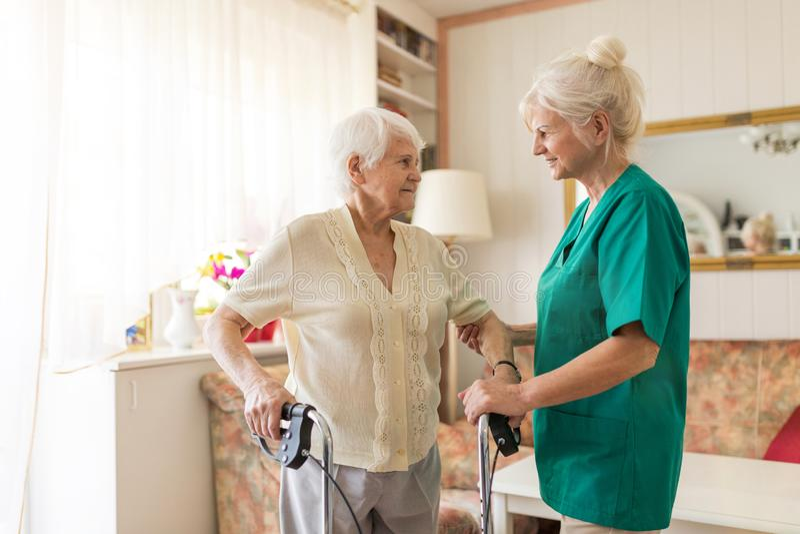 Νοσηλευτικός βοηθός που βοηθά την ανώτερη γυναίκα με το πλαίσιο περπατήματος στοκ φωτογραφία με δικαίωμα ελεύθερης χρήσης