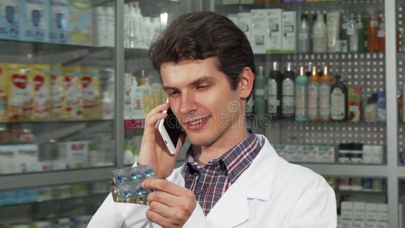 Νοσοκομειακός γιατρός που μιλά στο τηλέφωνο, που κρατά δύο φουσκάλες των χαπιών στοκ εικόνες