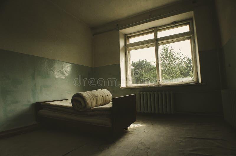Νοσοκομειακό κρεβάτι σε ένα δωμάτιο που εγκαταλείπεται στις καταστροφές με το φως που έρχεται μέσω των παραθύρων στοκ εικόνα με δικαίωμα ελεύθερης χρήσης