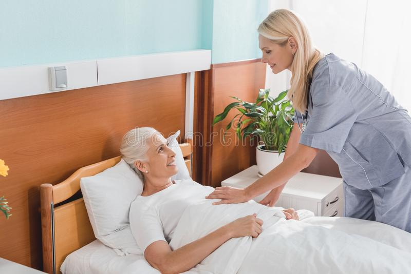 νοσοκόμα και ανώτερη γυναίκα που χαμογελούν η μια την άλλη στην περιποίηση στοκ εικόνα με δικαίωμα ελεύθερης χρήσης