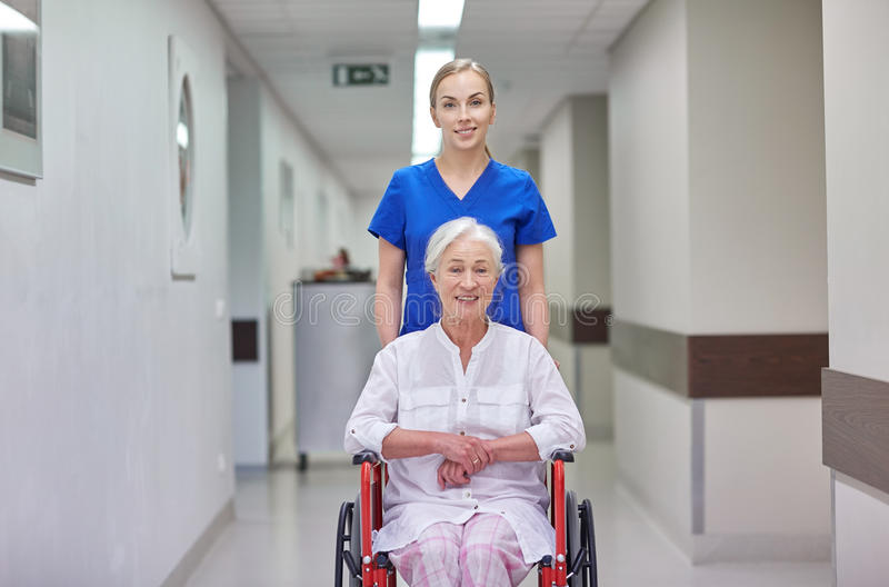 Νοσοκόμα με την ανώτερη γυναίκα στην αναπηρική καρέκλα στο νοσοκομείο στοκ εικόνες