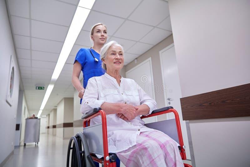 Νοσοκόμα με την ανώτερη γυναίκα στην αναπηρική καρέκλα στο νοσοκομείο στοκ φωτογραφία