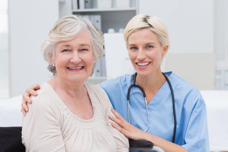 Νοσοκόμα με το βραχίονα γύρω από τον ανώτερο ασθενή στην κλινική στοκ φωτογραφία με δικαίωμα ελεύθερης χρήσης