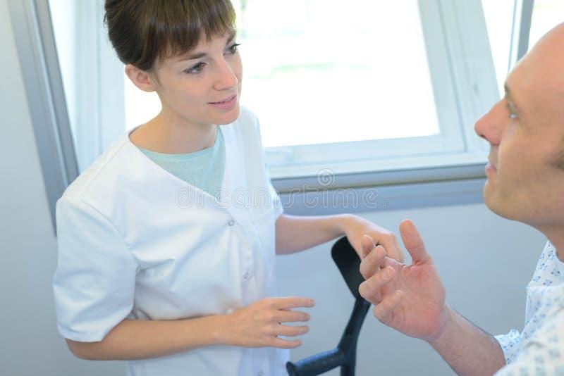 Νοσοκόμα που βοηθά επάνω τον ασθενή στοκ φωτογραφία