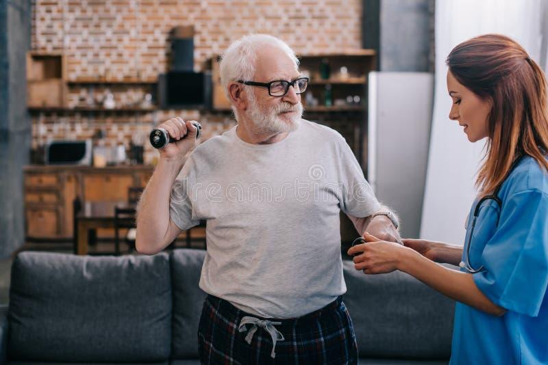 Νοσοκόμα που βοηθά την ανώτερη άσκηση ατόμων στοκ φωτογραφία με δικαίωμα ελεύθερης χρήσης