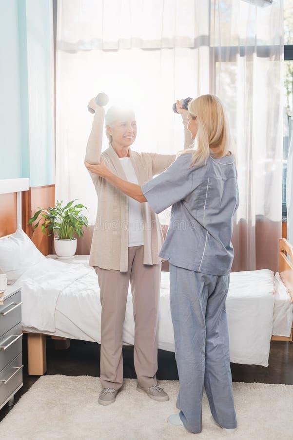 νοσοκόμα που βοηθά την ανώτερη άσκηση γυναικών με τους αλτήρες στην περιποίηση στοκ εικόνα