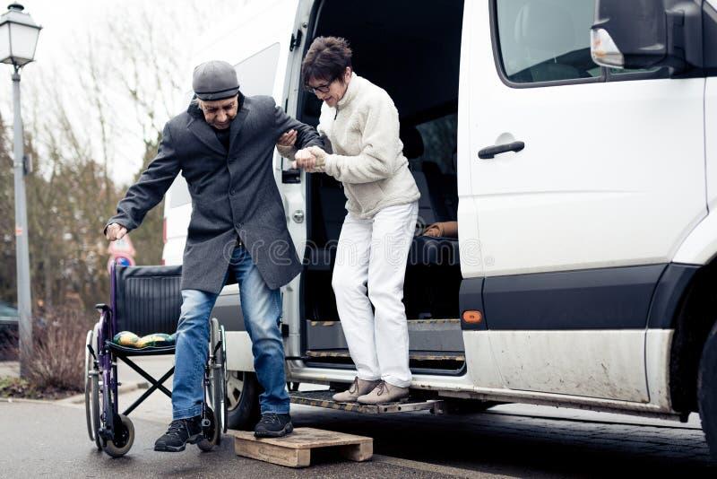 Νοσοκόμα που βοηθά την ανώτερη έξοδο ατόμων ένα φορτηγό στοκ φωτογραφία