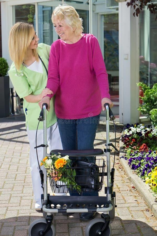 Νοσοκόμα που βοηθά την ανώτερη γυναίκα για να περπατήσει με τον περιπατητή στοκ εικόνες