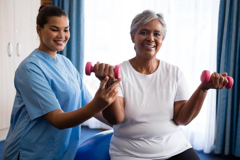 Νοσοκόμα που βοηθά την ανώτερη γυναίκα στην ανύψωση των αλτήρων στοκ φωτογραφία