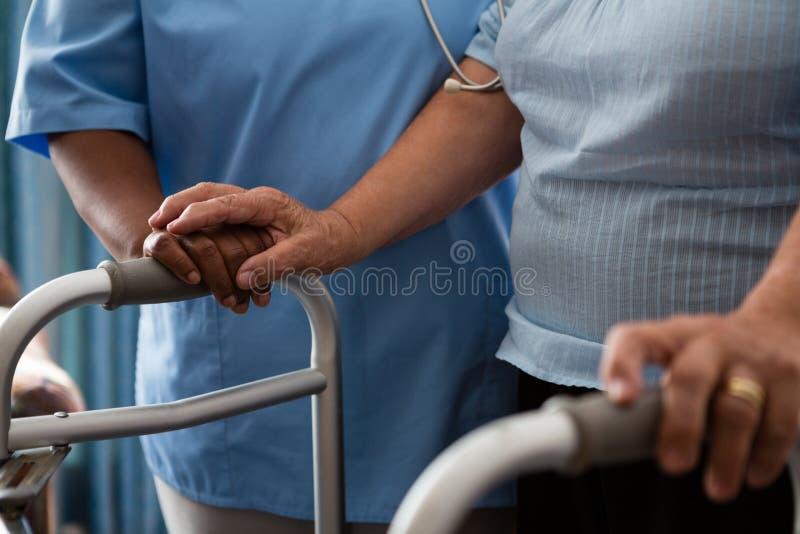 Νοσοκόμα που βοηθά τον ανώτερο ασθενή στο περπάτημα με τον περιπατητή στη ιδιωτική κλινική στοκ εικόνες