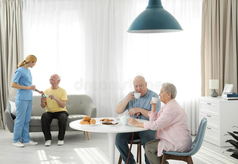 Νοσοκόμα που βοηθά το ηλικιωμένο άτομο ενώ ανώτερο ζεύγος που έχει το πρόγευμα στοκ εικόνες