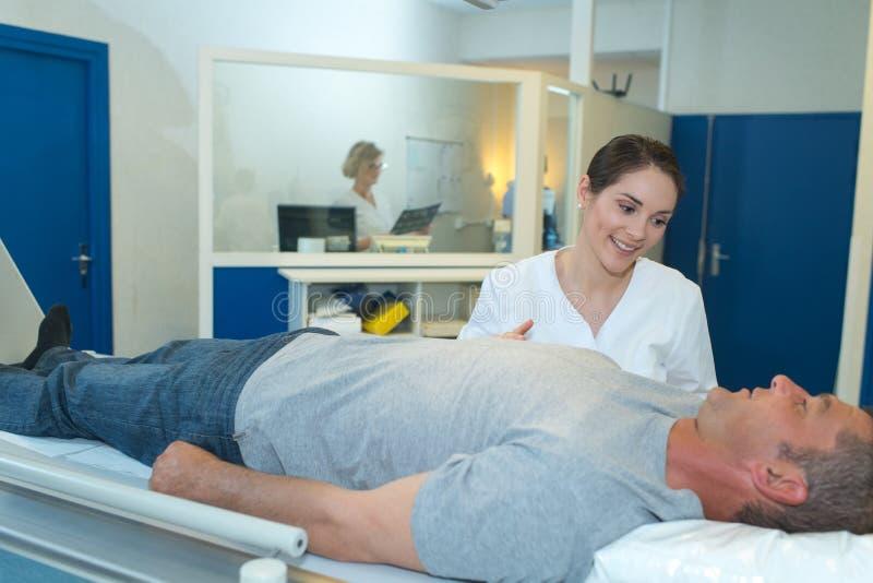 Νοσοκόμα που εξετάζει τον ασθενή πριν από την των ακτίνων X εξέταση στοκ φωτογραφίες