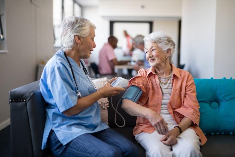 Νοσοκόμα που ελέγχει την ανώτερη πίεση του αίματος γυναικών στη ιδιωτική κλινική στοκ εικόνες με δικαίωμα ελεύθερης χρήσης