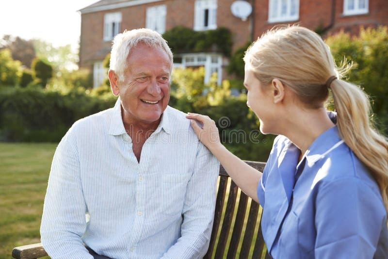 Νοσοκόμα που μιλά στο ανώτερο άτομο στο κατοικημένο σπίτι προσοχής στοκ φωτογραφία
