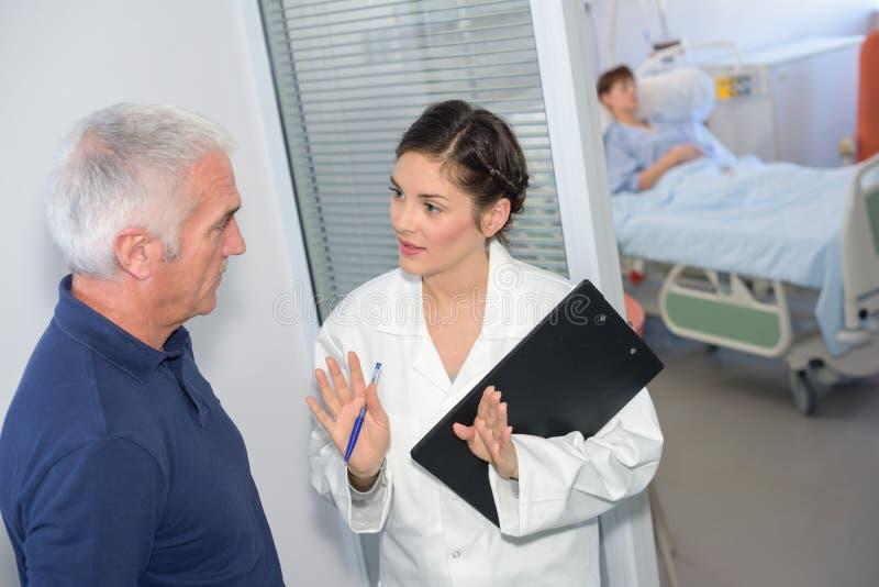 Νοσοκόμα που μιλά στο οικογενειακό μέλος έξω από το υπομονετικό δωμάτιο ` s στοκ φωτογραφία με δικαίωμα ελεύθερης χρήσης