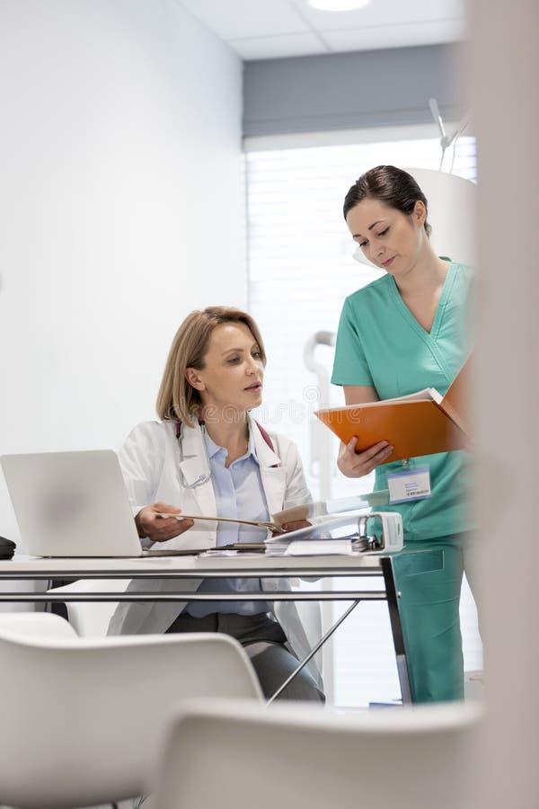 Νοσοκόμα που παρουσιάζει ιατρικό αρχείο για να ωριμάσει το γιατρό στο γραφείο στο νοσοκομείο στοκ φωτογραφία με δικαίωμα ελεύθερης χρήσης