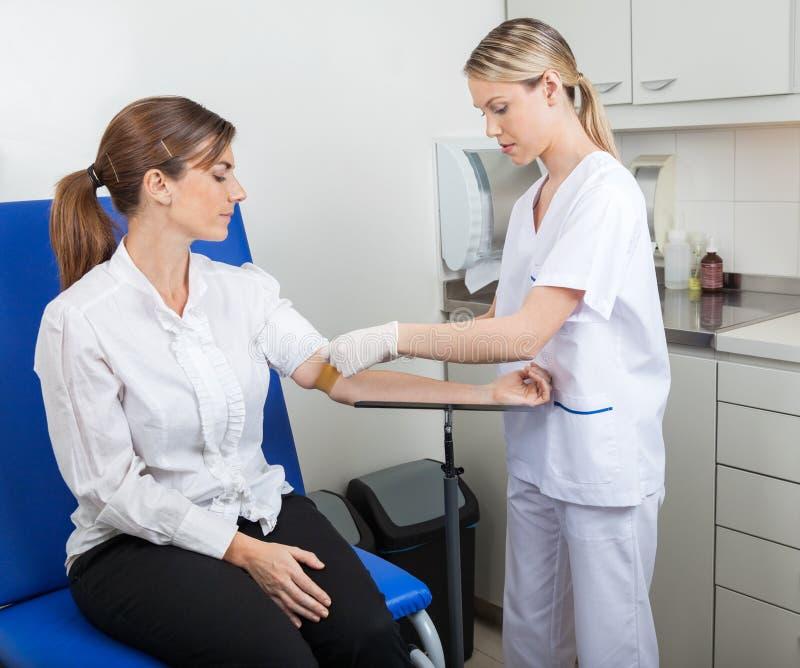 Νοσοκόμα που προετοιμάζει τη επιχειρηματία για τη εξέταση αίματος στοκ εικόνες
