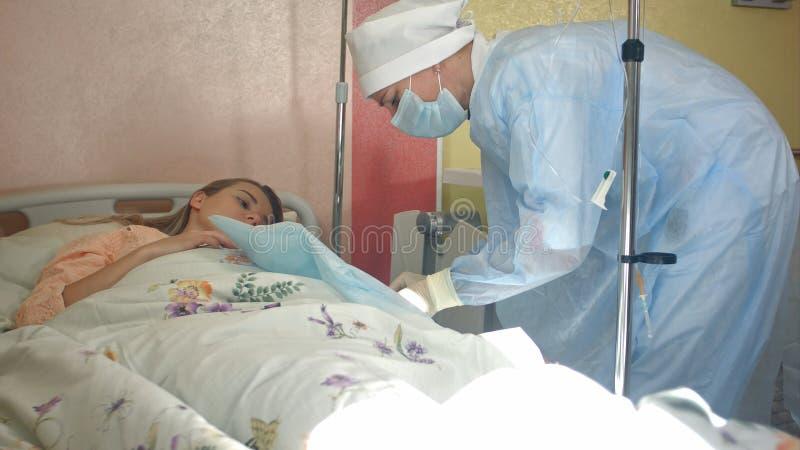 Νοσοκόμα που προετοιμάζει το θηλυκό υπομονετικό βραχίονα για να βάλει IV σωλήνα στοκ εικόνα