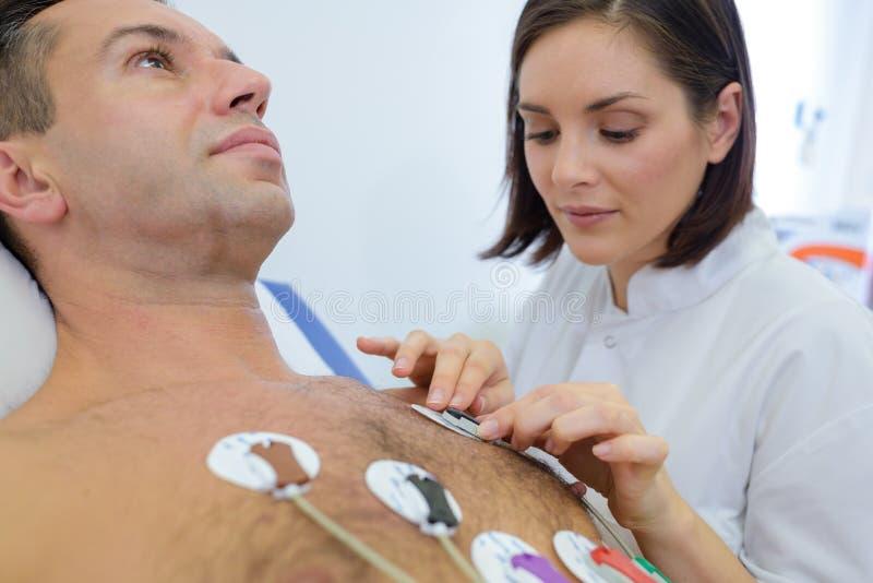 Νοσοκόμα που συνδέει το όργανο ελέγχου σωμάτων στοκ φωτογραφίες