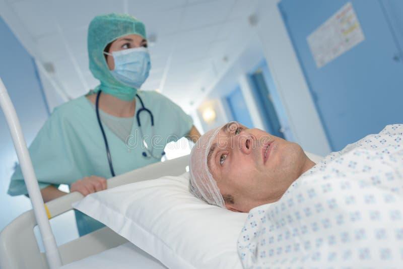 Νοσοκόμα που φέρνει τον αρσενικό ασθενή στο φορείο μετά από τη χειρουργική επέμβαση εγκεφάλου στοκ εικόνα με δικαίωμα ελεύθερης χρήσης