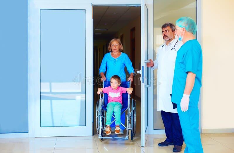 Νοσοκόμα που φροντίζει το μικρό ασθενή στην αναπηρική καρέκλα στο νοσοκομείο στοκ φωτογραφίες