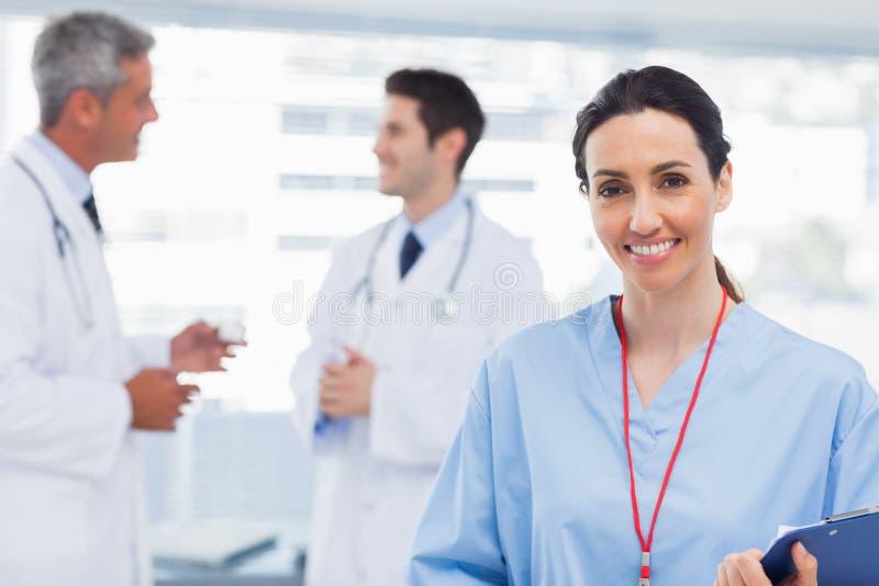 Νοσοκόμα που χαμογελά στη κάμερα ενώ οι γιατροί μιλούν από κοινού στοκ εικόνες με δικαίωμα ελεύθερης χρήσης