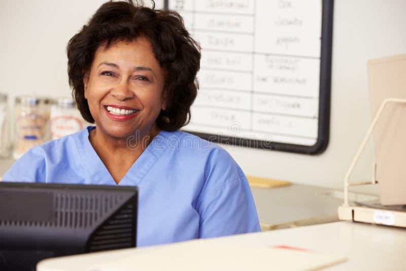 Νοσοκόμα που χρησιμοποιεί τον υπολογιστή στο σταθμό νοσοκόμων στοκ εικόνες