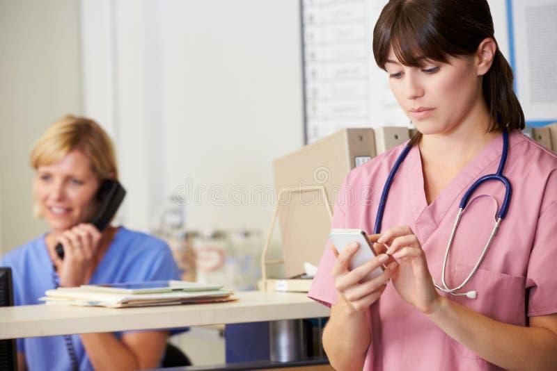 Νοσοκόμα που χρησιμοποιεί το κινητό τηλέφωνο στο σταθμό νοσοκόμων στοκ φωτογραφίες