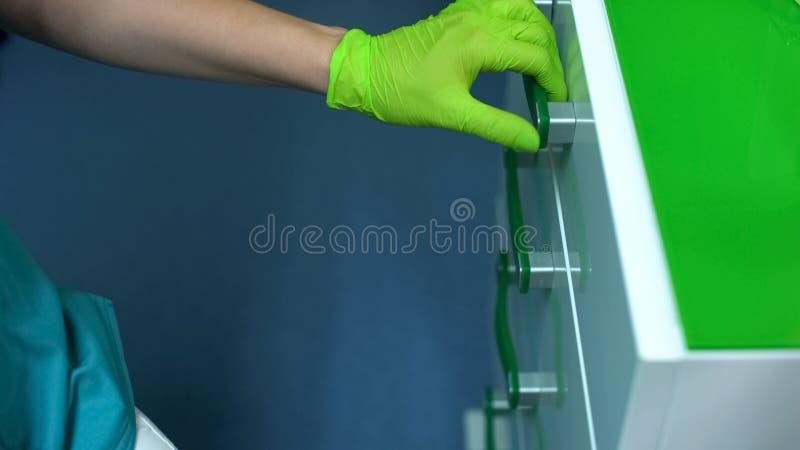 Νοσοκόμα στα χειρουργικά γάντια που ανοίγει το συρτάρι που παίρνει τα επαγγελματικά εργαλεία, σύγχρονη κλινική στοκ εικόνες με δικαίωμα ελεύθερης χρήσης