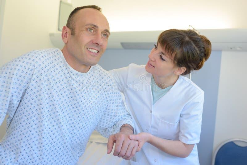 Νοσοκόμα στη ιδιωτική κλινική που βοηθά το άτομο που σηκώνεται από το κρεβάτι στοκ φωτογραφία