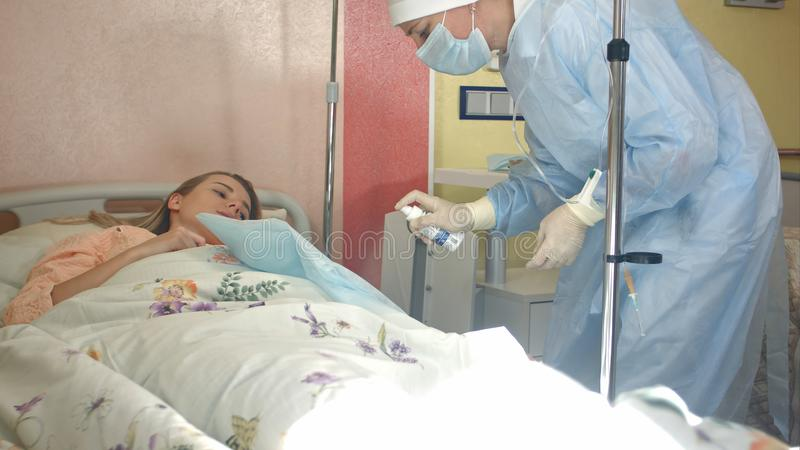 Νοσοκόμα στη μάσκα και γάντια που προετοιμάζουν τους θηλυκούς ασθενείς για dropper στοκ φωτογραφία με δικαίωμα ελεύθερης χρήσης