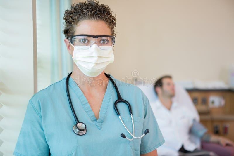 Νοσοκόμα στη προστατευτική ενδυμασία με τον ασθενή μέσα στοκ εικόνα με δικαίωμα ελεύθερης χρήσης
