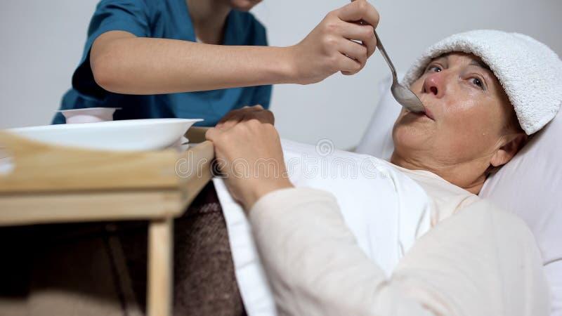 Νοσοκόμα του διανοητικού νοσοκομείου που ταΐζει την αδιάφορη γυναίκα με το κουάκερ, άσυλο στοκ φωτογραφίες με δικαίωμα ελεύθερης χρήσης