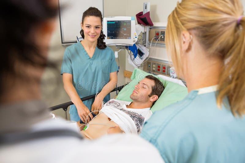 Νοσοκόμες και γιατρός που εξετάζουν τον ασθενή στοκ φωτογραφία με δικαίωμα ελεύθερης χρήσης