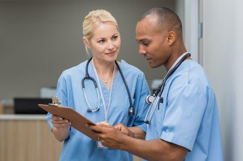 Νοσοκόμες που ελέγχουν τις ιατρικές εκθέσεις στοκ φωτογραφίες