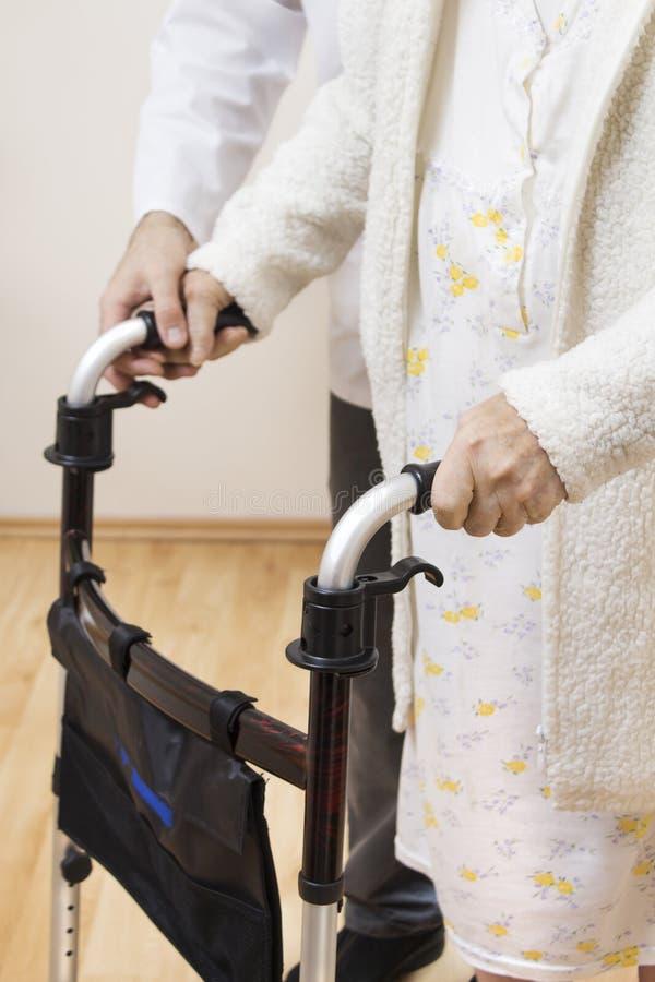 Νοσοκόμος κρατά το χέρι του σε ετοιμότητα της ηλικιωμένης γυναίκας, που βοηθά την για να περπατήσει με τη βοήθεια ενός μικρού μπα στοκ εικόνες