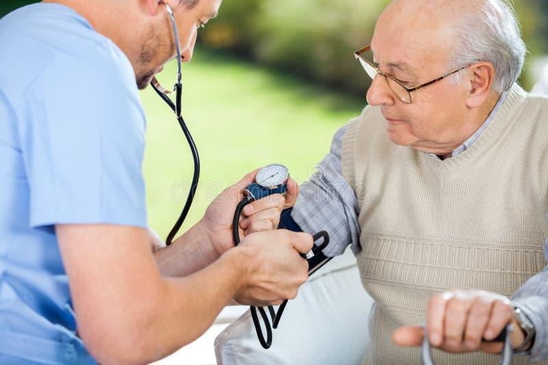 Νοσοκόμος που ελέγχει τη πίεση του αίματος του ανώτερου ατόμου στοκ εικόνες με δικαίωμα ελεύθερης χρήσης