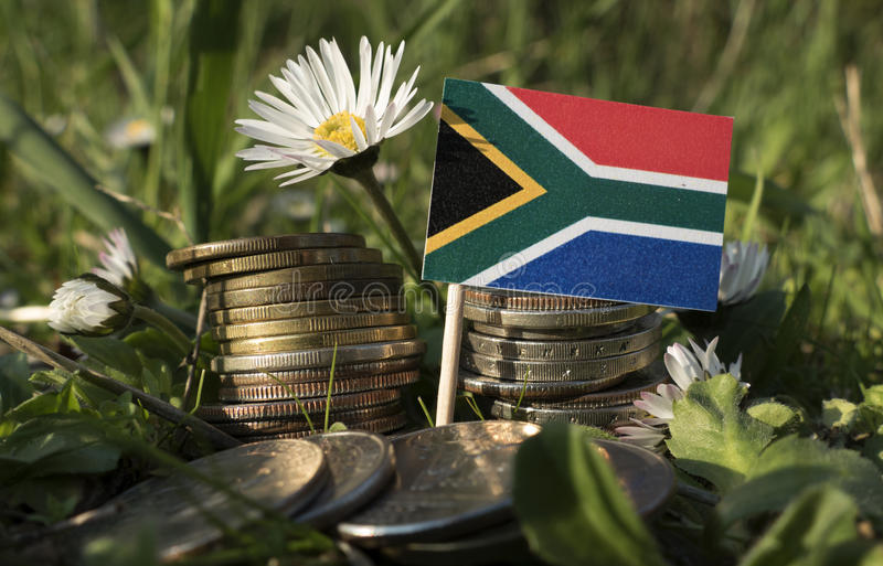 Νοτιοαφρικανική σημαία με το σωρό των νομισμάτων χρημάτων με τη χλόη στοκ φωτογραφία