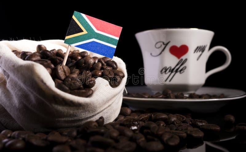 Νοτιοαφρικανική σημαία σε μια τσάντα με τα φασόλια καφέ που απομονώνονται στο Μαύρο στοκ φωτογραφία με δικαίωμα ελεύθερης χρήσης