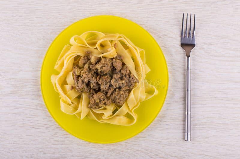 Νουντλς με τηγανισμένο mincemeat στο κίτρινο πιάτο, δίκρανο στον πίνακα στοκ φωτογραφίες